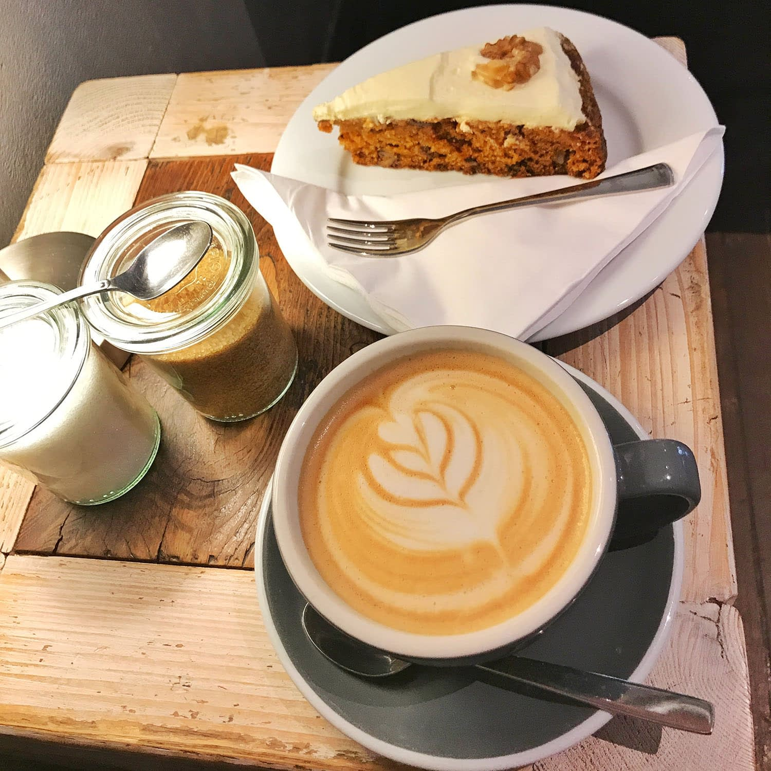 latte with leaf in the foam and a carrot cake on a wooden table