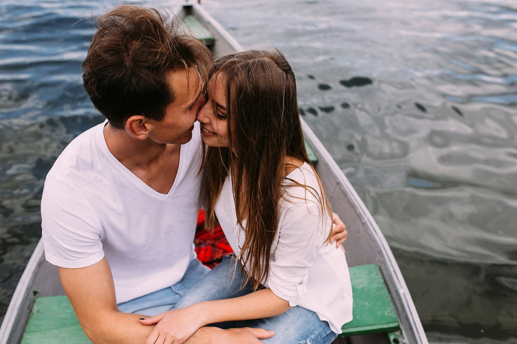 two people in love snuggling face to face in a boat